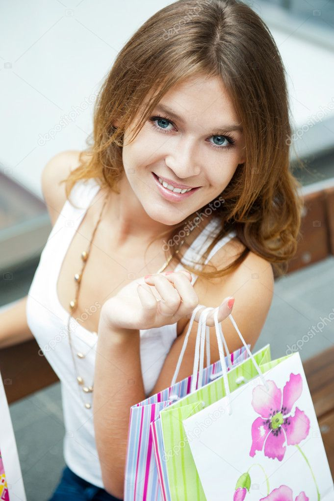 Photo of young joyful woman with shopping bags on the background of shop windows inside shopping mall — Stock Photo #6872693