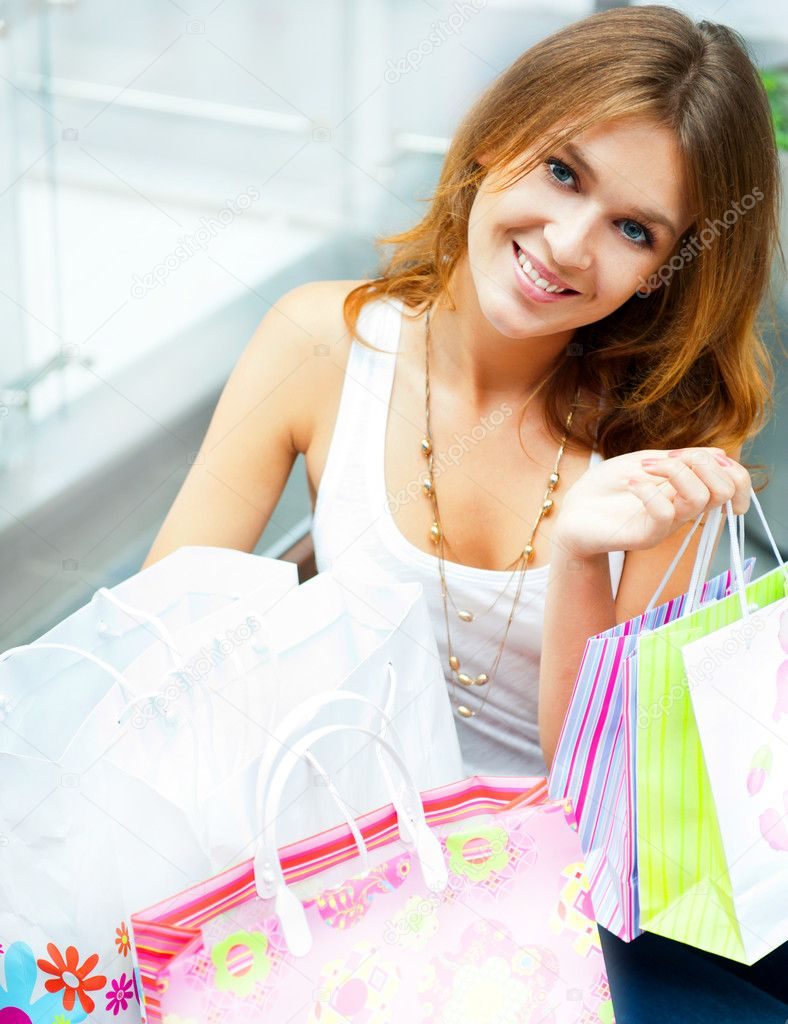 Happy woman at a shopping center with bags. Seasonal preparty shopping boom  Stock Photo #6872710