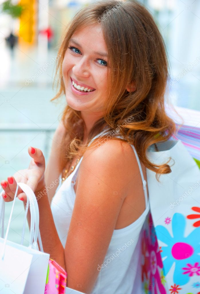 Happy woman at a shopping center with bags. Seasonal preparty shopping boom  Stock Photo #6872782