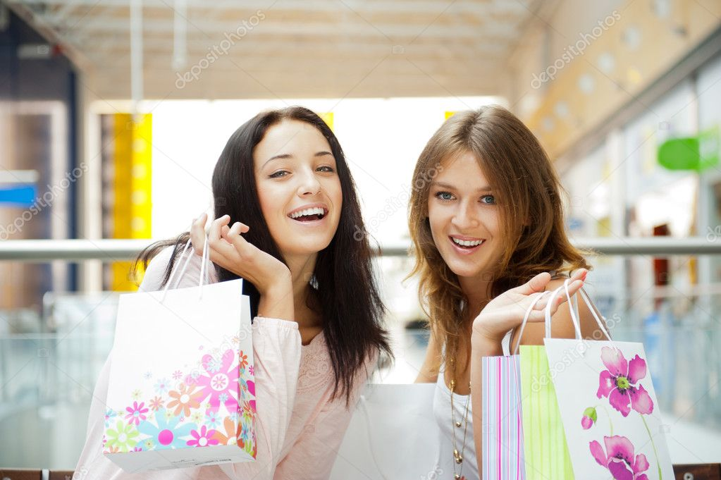 Two excited shopping woman together inside shopping mall laughing and gossip. Horizontal Shot — Stock Photo #6872805