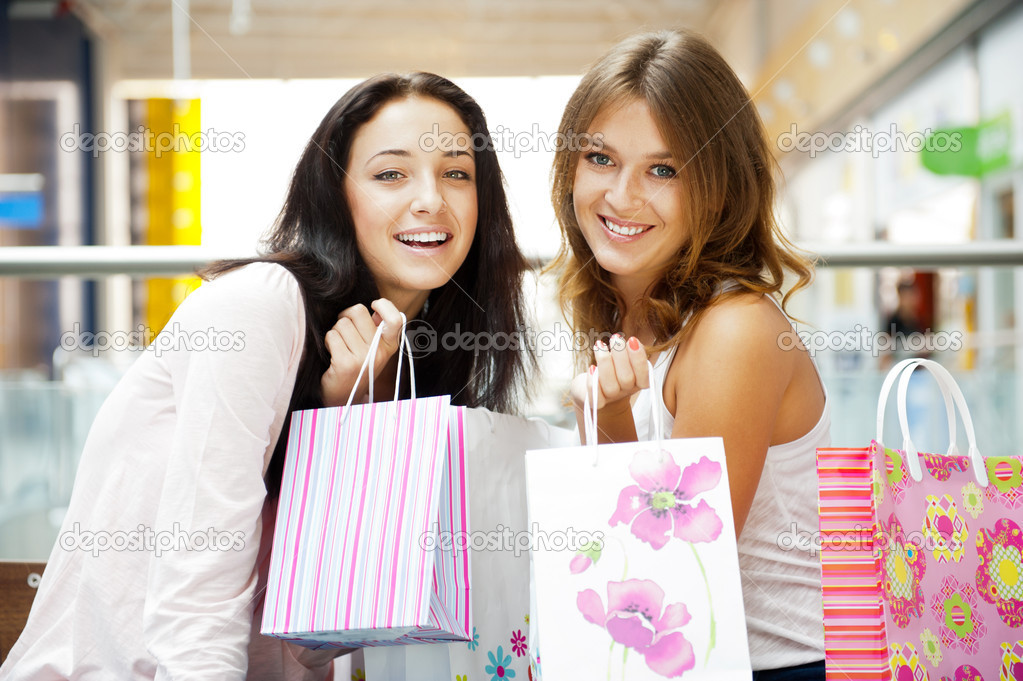 Two excited shopping woman together inside shopping mall laughing and gossip. Horizontal Shot — Stock Photo #6872821