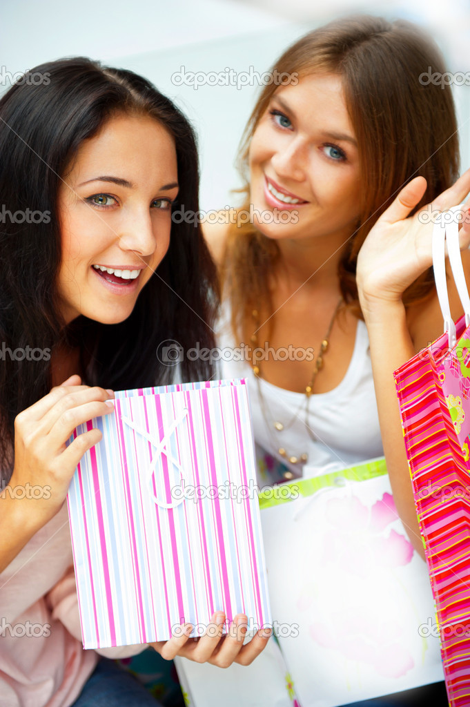 Two happy women at a shopping center with bags. Seasonal preparty shopping boom. — Stock Photo #6872855