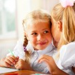 Stock Photo: Two little girls gossip in classroom