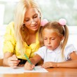 Teacher helps to little girls to make an exercises in classroom — Stock Photo