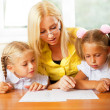 Teacher helps to little girls to make an exercises in classroom — Stock Photo #6939452