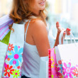 Closeup portrait of young happy woman with shopping bags at mall - Stock Photo