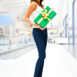 Beautiful brunette woman with a gift boxe standing inside shoppi — Stock Photo