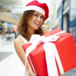 Excited attractive woman with big gift box standing at shopping — Stock Photo