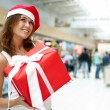 Excited attractive woman with big gift box standing at shopping — Stock Photo #6939523