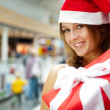 Excited attractive woman with big gift box standing at shopping — Stok fotoğraf