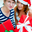Stock Photo: Young happy couple in Christmas hats standing togethe