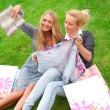 Portrait of two women relaxing on green grass after shopping. Ho — Foto Stock