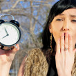Surprised woman holding alarm clock outdoors — Stock Photo