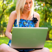 Vacker student kvinna med en laptop sitter på grönt gräs på — Stockfoto