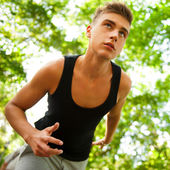 Closeup portrait of young man running in park — Stock Photo