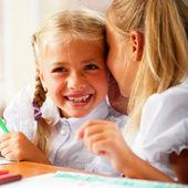 Two little girls gossip in classroom — Stock Photo