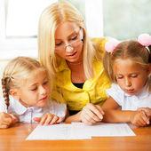 Enseignant aide aux petites filles à faire des exercices en salle de classe — Photo