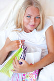 Young happy attractive girl unpack shopping bags in bedroom or h — Stock Photo