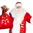 Santa Claus standing up on white background with his bag full of — Stock Photo #7039978