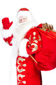 Santa Claus standing up on white background with his bag full of — Stockfoto