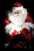Santa sitting at the Christmas room and looking into the sack — Foto Stock