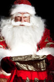 Santa sitter vid jul rum och tittar in i säcken — Stockfoto