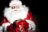 Santa seduto presso la camera di natale e alla ricerca nel sacco — Foto Stock