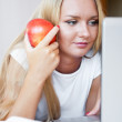 Smiling woman using a laptop while lying on her bed and eating r — Stock Photo #7040021
