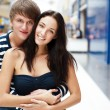 Portrait of young couple embracing at shopping mall and looking — Stock Photo