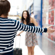 Royalty-Free Stock Photo: Young man meeting his girlfriend with opened arms at airport arr