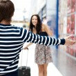Young man meeting his girlfriend with opened arms at airport arr — Stock Photo #7070693