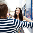 Young man meeting his girlfriend with opened arms at airport arr — Stock Photo #7070712