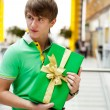 Portrait of young man inside shopping mall with gift box sitting — Stock Photo #7070724