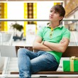 Portrait of young man inside shopping mall with gift box sitting — 图库照片