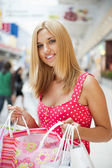 Bella donna in un centro commerciale con borse e sorridente — Foto Stock
