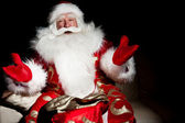Santa sedí s vnitřní pytel v temné noci pokoj — Stock fotografie