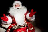 Santa sitter med en säck inomhus på mörka natt rum — Stockfoto