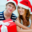Young happy couple in Christmas hats standing together and holdi — ストック写真
