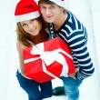 Young happy couple in Christmas hats standing together and holdi — Stockfoto