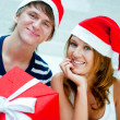 Young happy couple in Christmas hats standing together and holdi — Stok fotoğraf