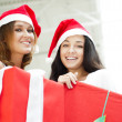 Young happy girls in Christmas hats.Standing together indoors an — Stock Photo