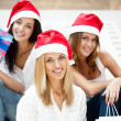 Group of three beautiful girls sitting on stairs at shopping mal — Stock Photo