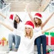 Group of three beautiful girls sitting on stairs at shopping mal — Stockfoto