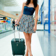 Royalty-Free Stock Photo: Young woman with luggage at the international airport. She is ve