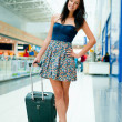 Young woman with luggage at the international airport. She is ve - Lizenzfreies Foto