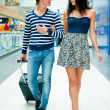 Portrait of young couple walking together at airport hall with t — Foto Stock