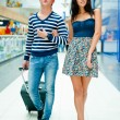 Portrait of young couple walking together at airport hall with t — ストック写真