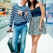 Portrait of young couple walking together at airport hall with t — Stockfoto