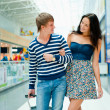 Portrait of young couple walking together at airport hall with t — Stock Photo