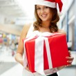 Young happy girl in Christmas hat. Standing indoors and holding — Stock Photo #7289364